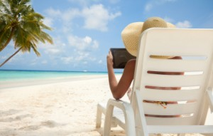 Woman with tablet computer on the beach sitting in the deck chair